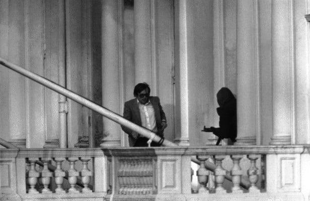Sim Harris making his escape across the first-floor balcony, as ordered by the masked SAS operator (far right) during the Operation NIMROD on May 5, 1980