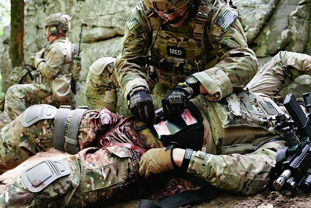 Special Operations Combat Medic applying tourniquet on wounded warrior - Navy SEAL Combat Medic