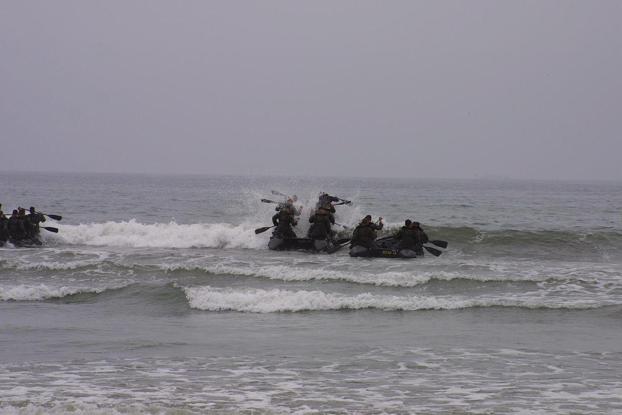 A platoon of Force Recon (FORECON) team operators paddle their Combat Rubber Reconnaissance Craft (CRRC) against the surf out to sea