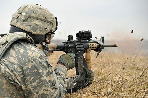 A soldier aiming through the scope mounted on his M4 Carbine