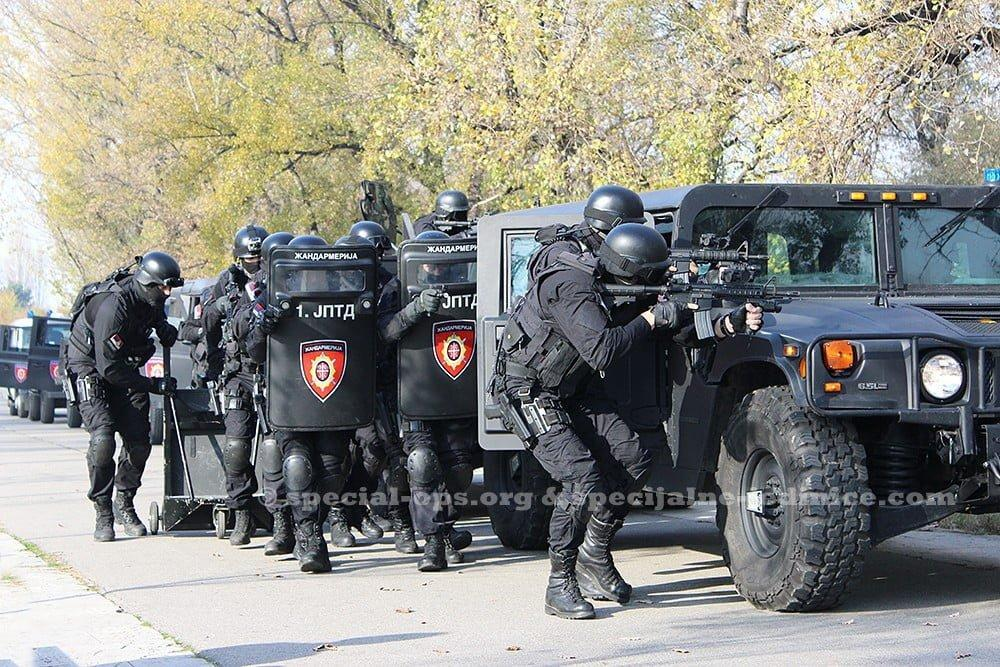 Serbian Gendarmerie operators brandishing their weapons behind the Humvees