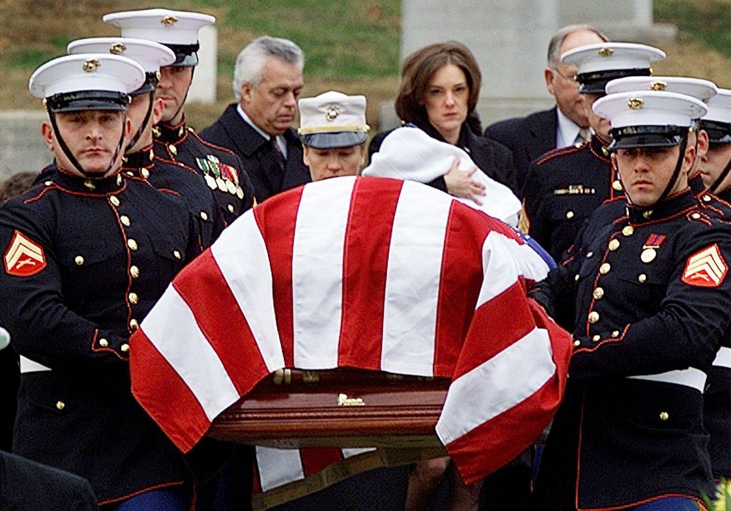 """Shannon Spann holds 6-month-old Jake as she walks behind the casket of Johnny """"Mike"""" Spann at Arlington National Cemetery on Dec. 10, 2001."""