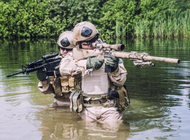Two U.S. Navy Seals navigating through swamp during the training