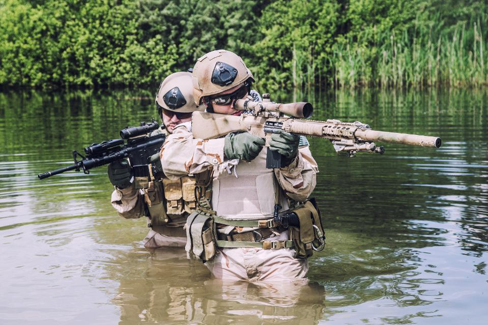 Two navy seals navigating through swamp
