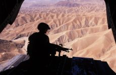 A silhouette of a flight engineer manning an M240 machine gun on the ramp of a CH-47D Chinook in eastern Afghanistan