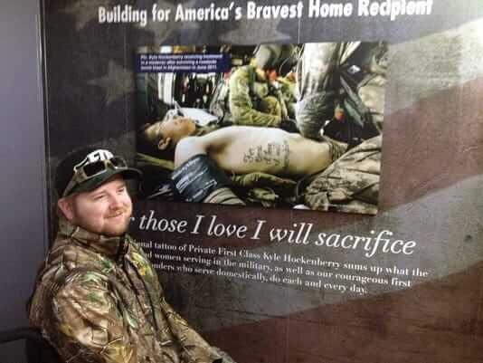 Pfc. Kyle Hockenberry posing in front of his iconic photo and tattoo For Those I love, I will sacrifice