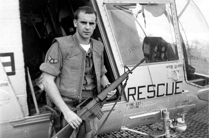 A1C William H. Pitsenbarger with an M16 outside the HH-43
