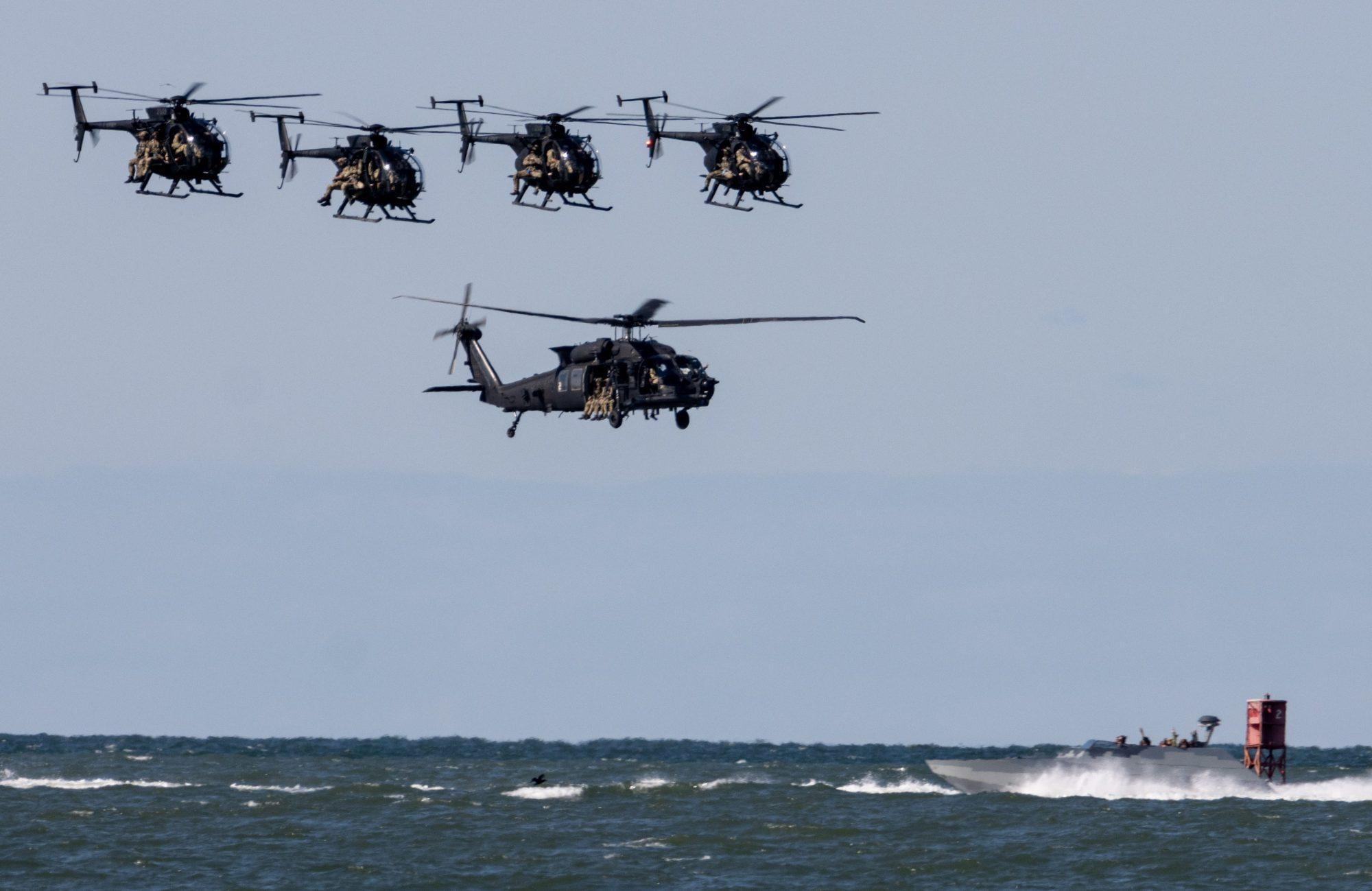 A formation of MH-6s along with an MH-60 low over the water with a CCA coming into view frame. The MH-6s often work with one or two MH-60s.