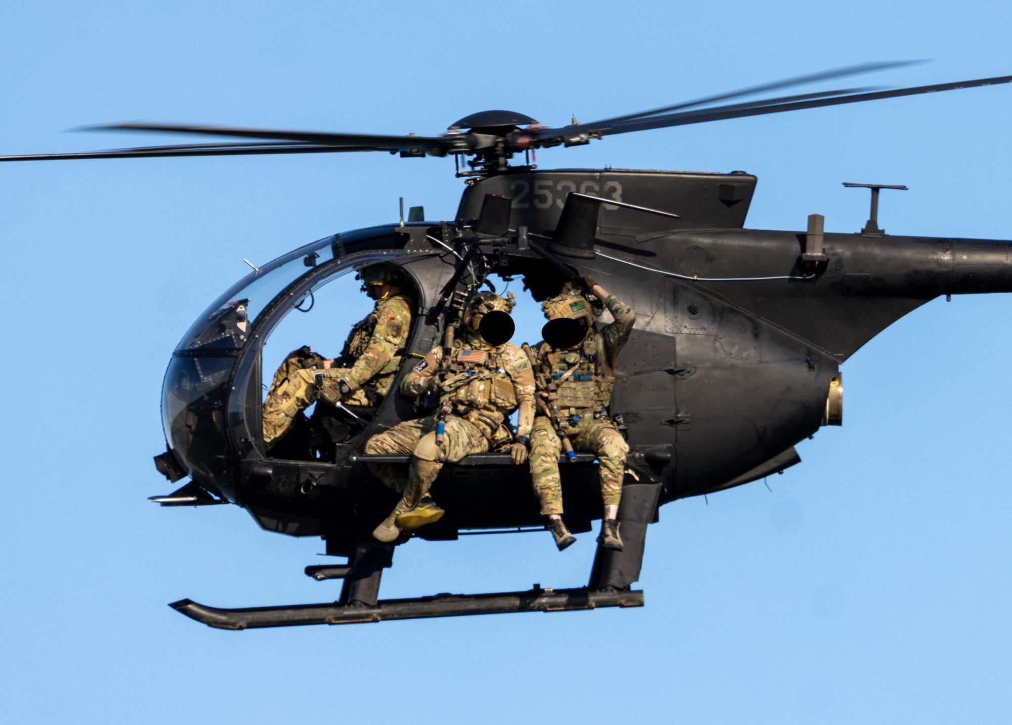SEAL operators sitting on the planks of the Little Bird