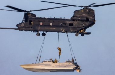 one of an MH-47 Chinook sling loading a stealthy Combat Craft Assault (CCA) boat while one of its crew, most likely a SWCC, fast ropes down into it in mid-air.