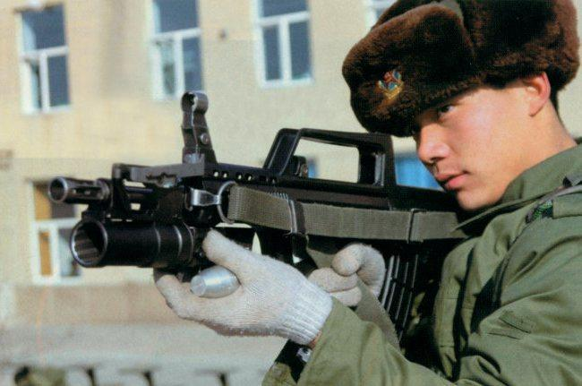 A Chinese soldier hodling an assault rifle with mounted QLG-10 underbarrel grenade launcher